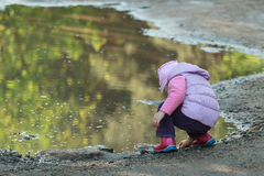 Tree years old girl looking for pebbles on big summer puddle bank Stock Images