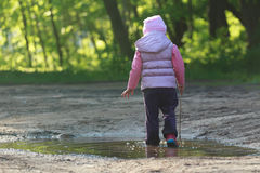 Tree years old girl walking in summer puddle with thin tree twig in hand Royalty Free Stock Photos