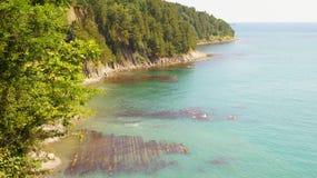 treed峭壁的美好的风景在黑海的天蓝色的水的旁边自在阳光下的白天 Tuapse,俄罗斯 库存照片