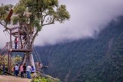 Treehouse giant swing in the Andes in Banos Ecuador. Banos, Ecuador on November 18, 2015: Tourists enjoying the giant swing at the treehouse Casa del Arbol in Stock Photos