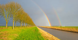 Trees along a canal below a rainbow. In sunlight stock images