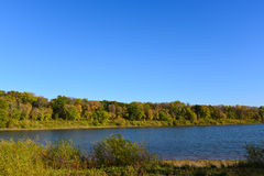Trees Along the Shore of Lake Cenaiko. These are trees lining the shore of Lake Cenaiko. This is at the Coon Rapids Dam Regional Park in Minnesota Stock Images