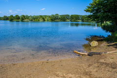 Trees Around the Lake. Clear blue lake - bright day - few clouds Stock Photo