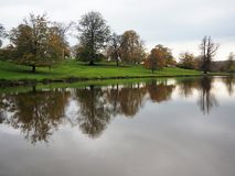 Trees with autumn leaves reflected in a lake, Ripley, North Yorkshire, UK. Trees with autumn leaves reflected on the surface of a lake at Ripley Castle, North stock photography