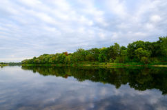 Trees on bank of pond and clouds are reflecting in water Royalty Free Stock Photos