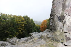 Trees from behind the rocks. View of autumn trees from behind the rocks of the castle royalty free stock photography