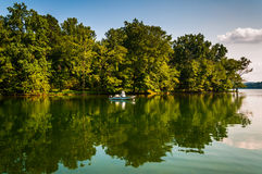 Trees and boat reflecting in Loch Raven Reservoir, near Towson, Stock Photo