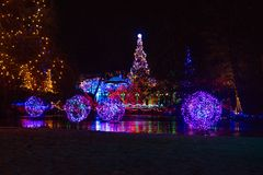Colorful light decorations for christmas at garden with reflections in lake. Trees and bushes decoarted with colorful light in a garden with reflections in the royalty free stock photos