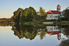 Trees and church mirroring on small pond Stock Images