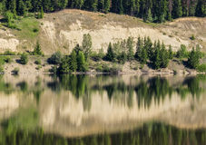 Trees and cliff reflected in still lake Royalty Free Stock Image