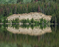 Trees and cliff reflected in still lake Royalty Free Stock Photography