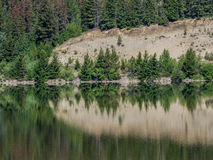 Trees and cliff reflected in still lake Royalty Free Stock Photo