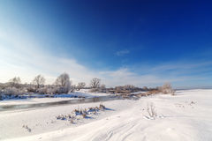 Trees covered with hoarfrost on  banks of a frozen river. Royalty Free Stock Photography