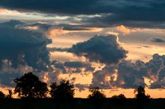 Dramatic clouds at sunset with silhouetted trees. Trees in the distance with dramatic clouds at sunset in Ontario, Canada royalty free stock photos