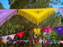 Trees dressed with colorful Manila shawls. Trees dressed with colorful Mantones de Manila Manila shawls in a Flamenco fair. Spanish Yarn bombing stock images