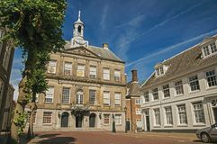 Trees and empty street in front of the City Hall building on sunny day in Weesp. stock image