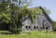 Trees frame an aging, wooden barn in a rural area. Rural areas have many aging and decaying structures such as this wooden barn Stock Image
