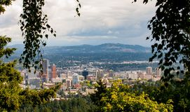 Portland Oregon skyline in late spring. Trees frame the hazy Portland Oregon Skyline just before a spring storm Stock Photography