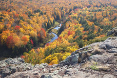 Trees in full autumn color and a small river viewed from rocky o Stock Photos