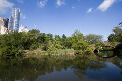 Trees and Gapstow bridge over the lake with blue sky at Central Park and buildings. Of Manhattan Royalty Free Stock Photography