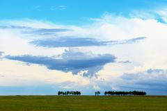 Trees on green field against epic cloudy blue sky. Blurred idyllic summer landscape with green grass on field, line of trees and amazing storm clouds, blue sky Royalty Free Stock Images