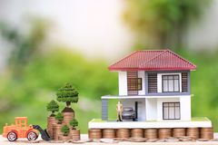 Trees growing on coins money and Truck toy with Miniature businessman standing on model house and the car on natural green royalty free stock photography