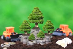 Trees growing on Stack of coins money and Truck toy on Natural g royalty free stock photo