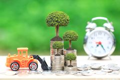 Trees growing on Stack of coins money and Truck toy on Natural green background, Real estate investments and Finance loan concept.  royalty free stock image
