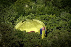 In the trees a hot balloon lands in a tight spot Royalty Free Stock Image
