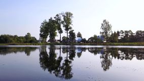 Trees and house reflected in the mirrored surface of the river. Aerial survey. Trees and house reflected in the mirrored surface of the river on a background of stock footage