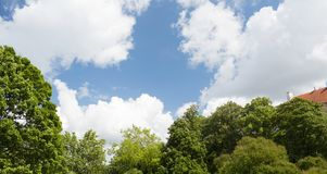 Trees and house roof over blue sky with clouds. Summer, season and nature concept - green trees and house roof over blue sky with white clouds Royalty Free Stock Photography