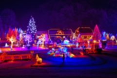 Trees and houses in christmas lights blurred view. On beautiful snowy winter night stock images