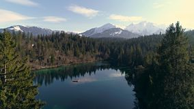Between Trees Lake Mountain Aerial 4k. Aerial footage of a beautiful lake in the forest with mountains in the background. Shot in Flims, Switzerland in 4k stock video