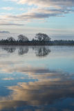 Trees lake shore clouds reflection in lake Royalty Free Stock Image