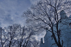 Trees without leaves on the background of an old gloomy house and clouds in the evening sky, sadness.  Stock Images