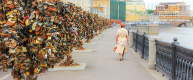 Trees locked in love. A middle aged woman walks by love trees in Moscow Stock Photography