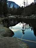 Reflection on Mirror Lake in Yosemite. Trees, mountains, sky clouds, and plane contrail reflected on still water. Winter in Yosemite National Park. Rocks and Stock Photo