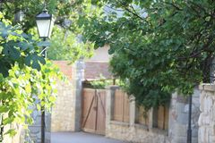 Stone road, stone walls, wooden door, lantern pillar and trees stock image