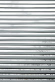 Trees seen through semi-closed metallic blinds Royalty Free Stock Photo