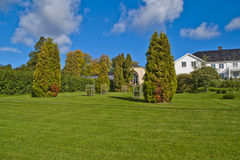 Trees, shrubs and hedges in the garden of red mansion. Red mansion in halden has a large baroque garden and can boast of beautiful trees, shrubs, hedges and royalty free stock photos