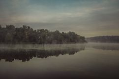 Trees Under Gray Sky Beside Glassy Water Royalty Free Stock Photos