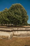 Trees and wall that forms part of the palace's moat of Les Invalides in a sunny day at Paris. Stock Images