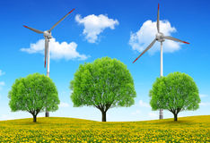 Trees with wind turbines on meadow Stock Photos