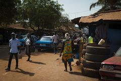 Treet scene in the city of Bissau with people walking along a dirt road in a slum, in Guinea-Bissau. Bissau, Republic of Guinea-Bissau - January 29, 2018: Street Royalty Free Stock Images