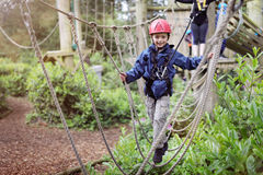 Treetop adventure park. Boy in a harness on a treetop adventure park walking across a rope bridge royalty free stock photo