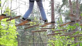 Treetop adventure park at daytime. Ropes and wooden planks. Keep balance and be careful stock video