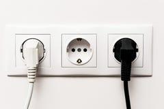 Trefaldig elektrisk hålighet med två pluggade kablar Arkivfoto
