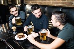 Treffen der besten Freunde Drei glückliche junge Männer in der Freizeitkleidung sprechend und trinkendes Bier beim in der Bar zus lizenzfreies stockbild