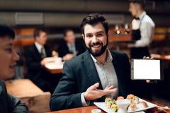 Treffen von chinesischen Geschäftsmännern im Restaurant Mann zeigt Tablette lizenzfreie stockfotos
