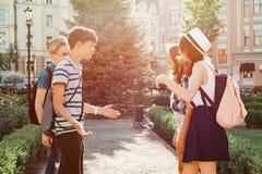 Treffen von lächelnden Freundjugendlichen in der Stadt, glückliche junge Leute, die, umarmend sich grüßen, hoch fünf gebend Freun lizenzfreie stockbilder